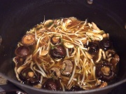 Broth turned off on the stove with mushrooms and sprouts added to absorb flavor