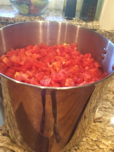 Tomatoes go into the stainless steel pot